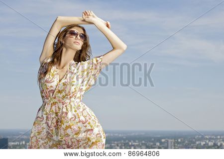 portrait of a beautiful attractive and sensuality young adult pretty brunette woman in sunglasses on background blue sunlight sky