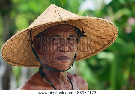 Portrait Of An Unidentified Old Balinese Farmer With A Wrinkled Face In Traditional Straw Wide-brimm
