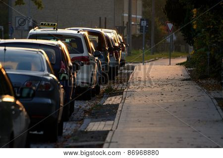 Parking Cars With A Taxi Along Pavement
