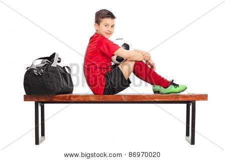 Junior soccer player in a red jersey, holding a ball and sitting on a wooden bench isolated on white background