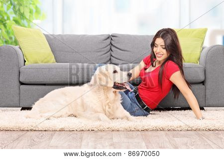 Young girl relaxing with her dog seated on the floor by a modern gray couch at home