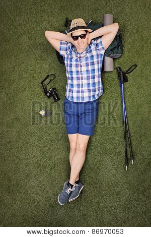 Full length vertical shot of a male hiker lying on his backpack in a grass field with his hiking equipment around him