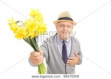 Kind senior gentleman giving flowers to someone and looking at the camera isolated on white background