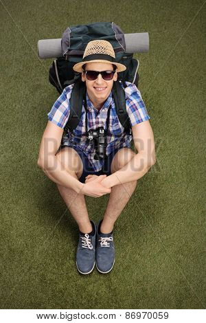 Vertical shot of a cheerful young hiker sitting on grass, carrying a backpack with hiking equipment and looking at the camera