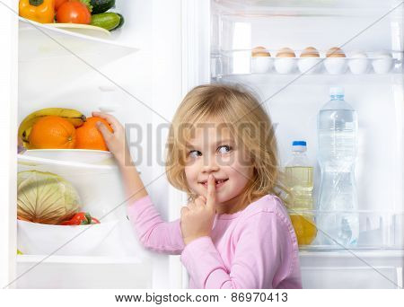 Little cute girl making silence sign near open fridge