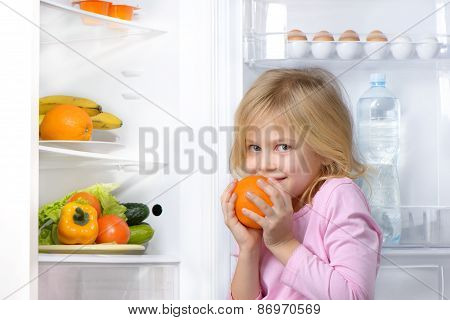 Little girl holding orange near open fridge