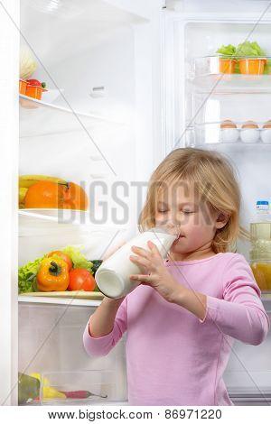 Little cute girl drinking milk near open fridge