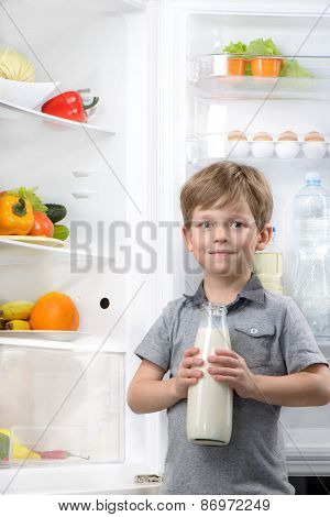 Little cute boy holding bottle of milk near open fridge
