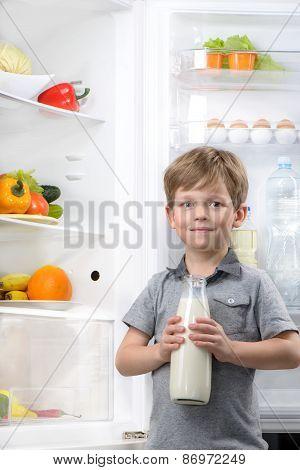 Little cute boy holding bottle of milk near open fridge