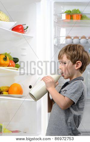 Little boy drinking milk near open fridge