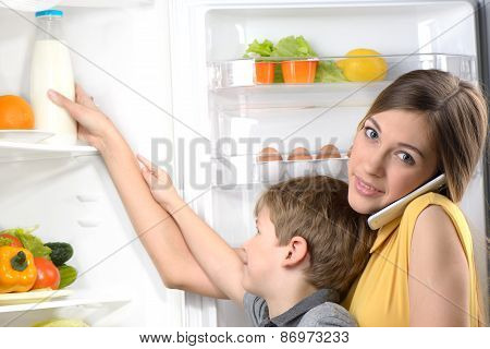 Young mother helping her son to get milk from fridge