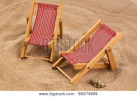 a small deck chair  on a sandy beach. symbolic photo for vacation, holiday, travel