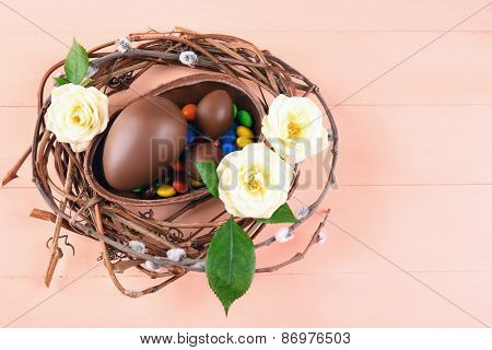 Chocolate Easter eggs with flowers in wicker nest, closeup