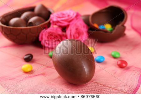 Chocolate Easter eggs with flowers on color tulle, closeup