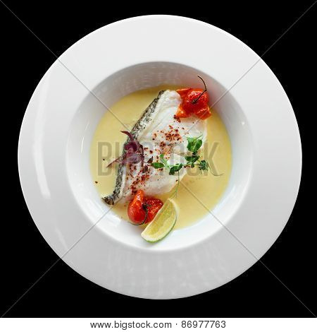 Chilean seabass fillet in plate, isolated on black background