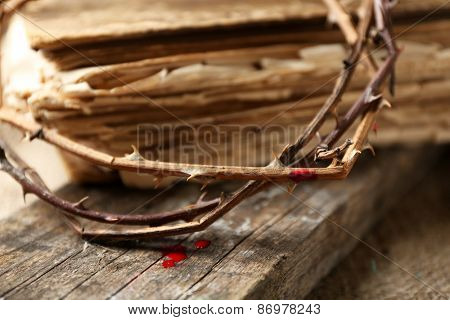 Crown of thorns with blood and bible, close up