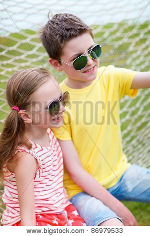 Teenage boy taking selfie with his little sister outdoors on summer day