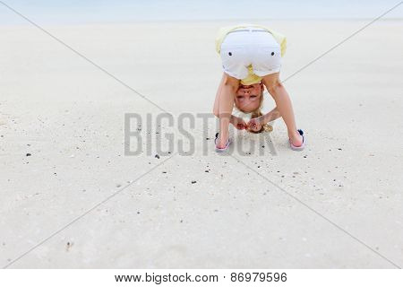 Playful little girl at beach during summer vacation