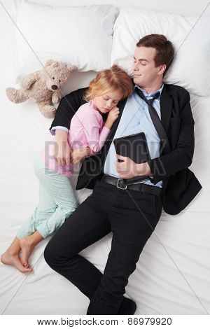 Top view of businessman with tablet computer and sleeping daughter
