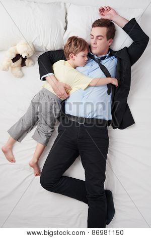 Top view of businessman and his sleeping little son