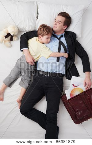 Top view of businessman with briefcase and his sleeping son