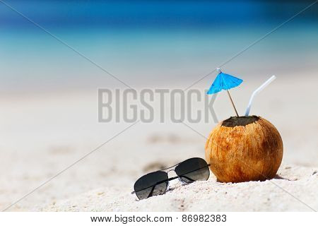 Tropical cocktail in a coconut on a beautiful beach