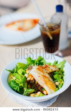 Delicious fresh caesar salad with grilled chicken served for lunch at restaurant