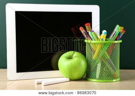 Digital tablet,  colorful pens and apple on desk in front of blackboard
