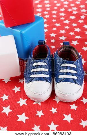 Baby shoes on red background