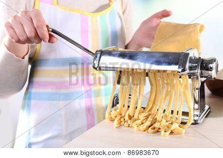 Woman making noodles with pasta machine, closeup