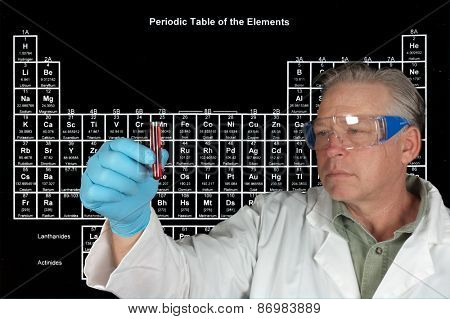 Scientist studying a vial of chemical in front of a Periodic table of Elements