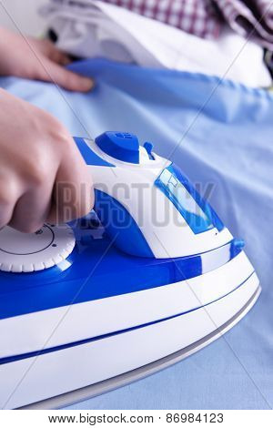 Female hand ironing clothes on ironing board, closeup