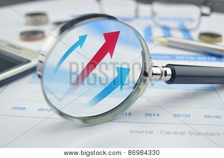 Rising Red And Blue Arrow On Magnifying Glass
