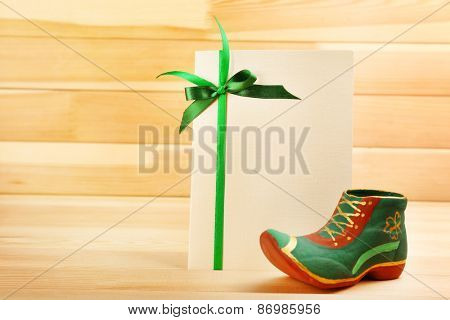 Greeting card for Saint Patrick's Day with leprechaun shoe on wooden planks background