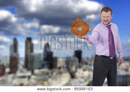 Businessman holding his right hand out, palm up with sphere with modern city in background