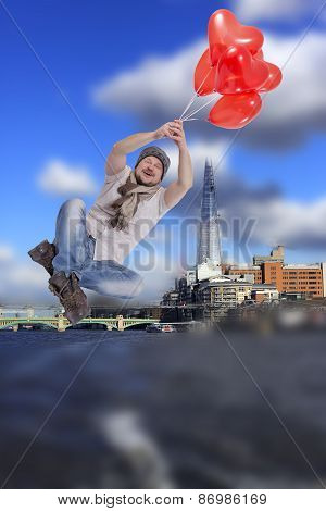 Young man flying on balloons with modern city in background