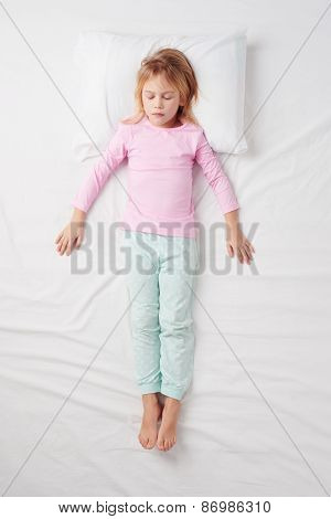 Top view of little girl sleeping in Soldier pose