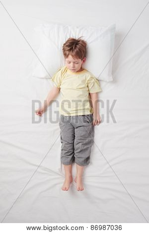 Top view of little boy sleeping in Soldier pose
