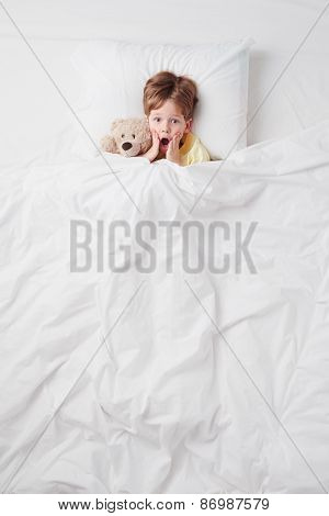 Top view of little scared by nightmares boy under blanket