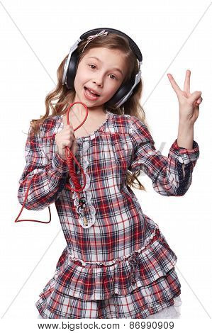 Pretty little girl singing in imaginary microphone with headphones on his head isolated over white b
