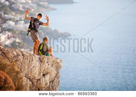 Young couple on rock and enjoying beautiful view