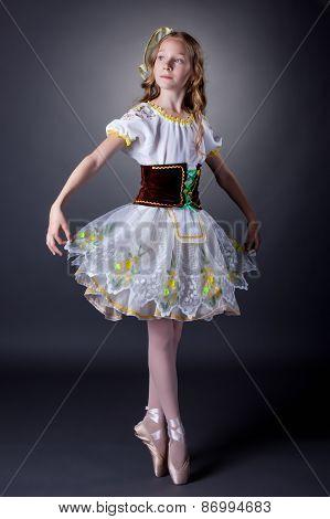 Charming young ballerina dancing in folk costume