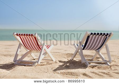 Two Deckchairs On Beach