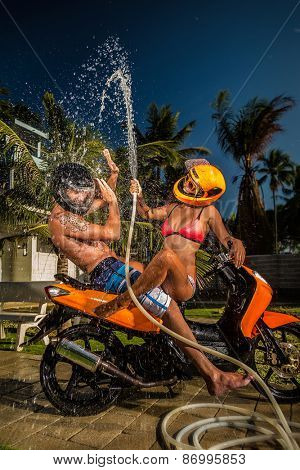 Portrait of glamorous young couple having fun with garden hose splashing summer rain on scooter