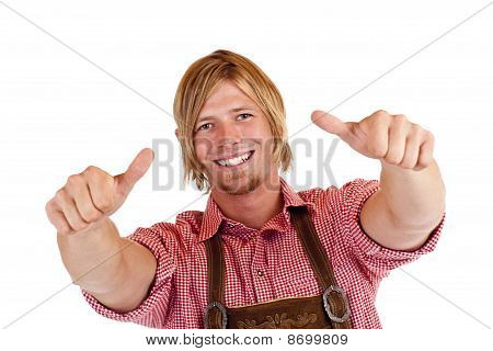 Bavarian man with oktoberfest leather trousers (Lederhose) shows both thumbs up.