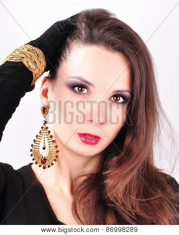 young beautiful dark-haired girl in extravagant earrings