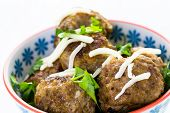 stock photo of cilantro  - Homemade Italian meatballs garnished with cilantro and parmesan cheese in a small bowl - JPG