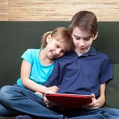 foto of half  - Children wearing casual clothes playing or watching a movie on a touch pad at home sitting on a green sofa - JPG