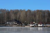 foto of tree house  - houses three white and one gray on the shores of Lake   covered with shiny ice.Around houses high birches.On ice reflection of trees and houses.Clear blue sky.Winter day. Koltushi village Leningrad region Russia - JPG