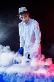 stock photo of mad scientist  - Smiling man scientist with dry ice show - JPG